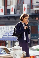 Businesswoman talking on phone on urban street