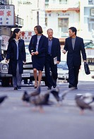Group of businesspeople walking and talking on urban street
