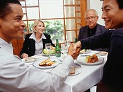 Businessmen shaking hands over lunch in restaurant