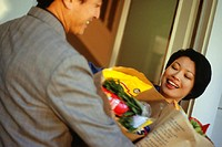 Man handing woman bags of groceries outside house
