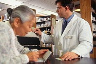 Pharmacist selling medicine to senior woman in pharmacy