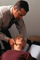 Chiropractor examining patients cervical vertebrae in clinic