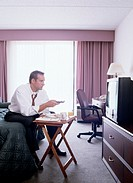 Businessman Watching TV in Hotel Room