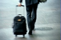 Low Section of Businessman Walking with Suitcase