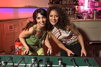 portrait of two female friends playing tabletop football