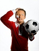 Young man with Poland flag painted on face holding soccer ball, eyes closed