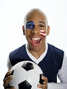Man with USA flag painted on face, holding football