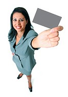 an adult ethnic looking woman in a grey business outfit smiles up into the camera as she holds up a  card