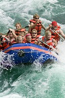 lifestyle shot of a group of people as they ride the rapids while white water rafting