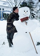 Man kissing snowman with broom