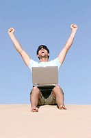 Man sitting on sand with laptop, arms out, low angle view