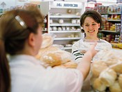 a caucasian woman purchases baked goods at a supermarket being aided by an employee