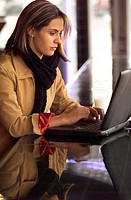 lifestyle photograph of an attractive caucasian female as she works on her laptop computer