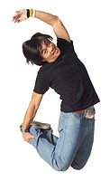 an asian teenage male in jeans and a black shirt jumps up wildly through the air
