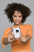 medium shot of a young adult female as she uses her digital camera