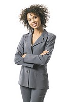 portrait of a young adult business woman in a grey suit as she folds her arms and smiles