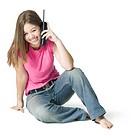 full length youth portrait of a teenage female as she sits and chats on the phone