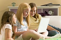 teenage lifestyle shot of three girls as they sit on the bed and work on a laptop computer