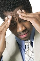 business portrait of an adult male in a suit as he holds his head as if stressed out