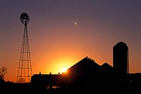 Sun rising over farm buildings with a windmill