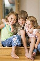lifestyle portrait of three siblings as they put their arms around each other and smile