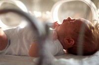 close up of a caucasain newborn baby laying in an incubator and crying