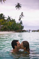 a caucasian couple swim together and kiss in the water while they vacation in the tropics