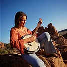 a young woman in blue jeans and a red long sleeved shirt is sittingn on the crest of a boulder playing a banjo with the blue sky and other rock croppi...