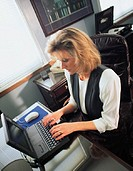 A blonde woman in a white shirt and black vest sits at a desk while typing on a laptop computer in an office