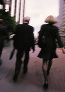 A BLURRED BUSINESSMAN DRESSED IN A SUIT  AND A BUSINESSWOMAN IN A BLACK DRESS WALK AS THEY CONVERSE OUTSIDE