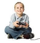 full body shot of a male child as he sits and uses a video game controler