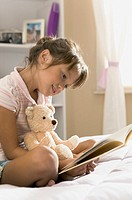 lifestyle portrait of a female child in a pink striped shirt as she sits in her bedroom and read a book