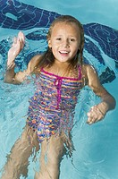 lifestyle portrait of a female child as she swims through a pool and smiles at the camera