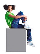 a younng african american girl in jeans and a green shirt sits atop a blank sign