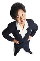 an attractive asian woman in a blue pant suit puts her hands on her hips and smiles up at the camera