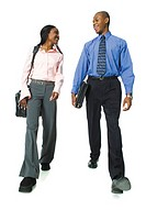 two young african american business people walk along having a conversation