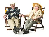 Elderly couple happily lounge in patio chairs.