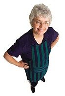 Birdseye view of an elderly woman wearing an apron smiles up at the camera.