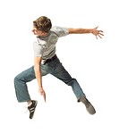 a caucasian male teen in jeans and a grey shirt jumps and spins through the air