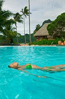 an attractive caucasian woman floats on her back in a swimming pool at a tropical resort