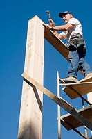 Carpenter standing on scaffolding hammering a nail into a sill plate to connect it to the corner stud of a two-story room.