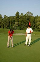 A teenage girl plays golf on a putting green as a man looks on