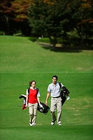 Front view of a couple walking on the fairway as they carry their golf bags
