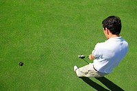 Male golfer making a putt