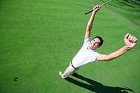 Male golfer clenching his fists in excitement after a making a putt