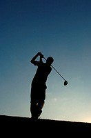 Silhouette of a man in action hitting a golf shot