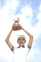Low angle view of a woman raising a golf trophy in excitement