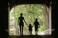 Silhouette of mom with two children in covered bridge. Pennsylvania, USA