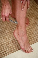 Sexy caucasian woman in shower nude shaving legs