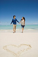 Newlyweds on beach near heart shape